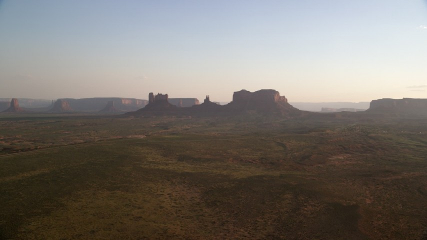 Flying by buttes and mesas, Monument Valley, Utah, Arizona, twilight Aerial Stock Footage | AX133_117