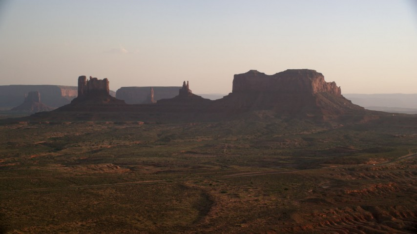 Flying by buttes, highway, Monument Valley, Utah, Arizona, twilight Aerial Stock Footage | AX133_118
