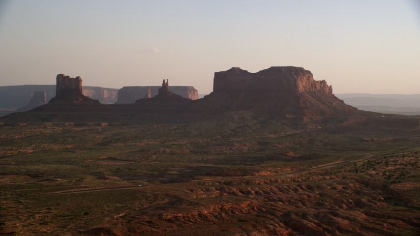 Flying by buttes, highway, Monument Valley, Utah, Arizona, twilight  Aerial Stock Footage | AX133_119