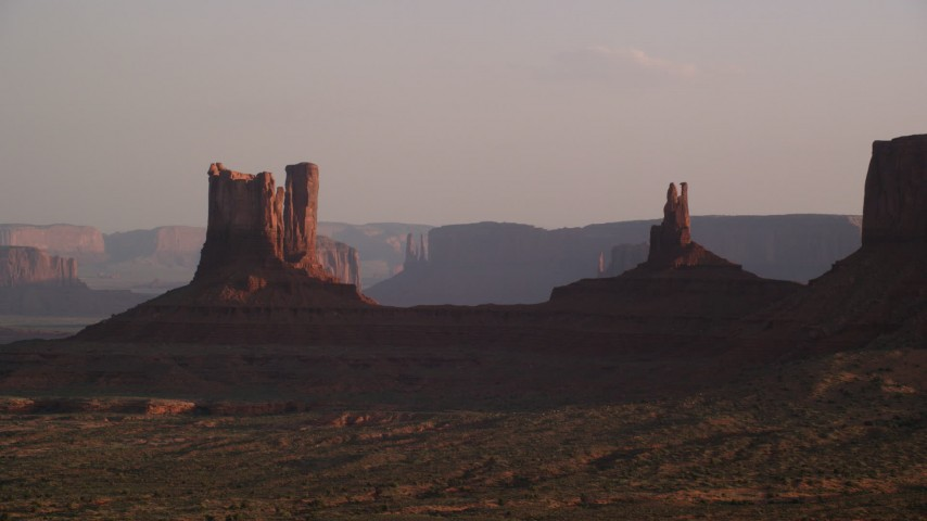 Flying by buttes, hazy day, Monument Valley, Utah, Arizona, twilight Aerial Stock Footage | AX133_122