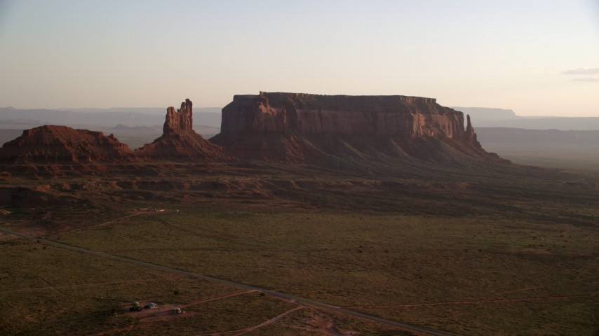Flying by Setting Hen Butte, Eagle Mesa, Monument Valley, Utah, Arizona, twilight Aerial Stock Footage | AX133_125