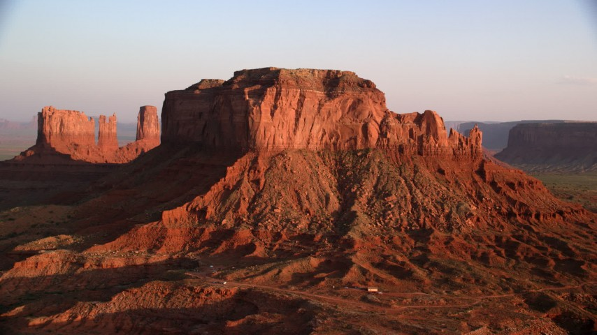 Approaching Brighams Tomb Butte, Monument Valley, Utah, Arizona, sunset Aerial Stock Footage AX133_127