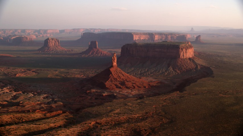 Flying by Big Indian Butte, other buttes, Monument Valley, Utah, Arizona, twilight Aerial Stock Footage | AX133_131
