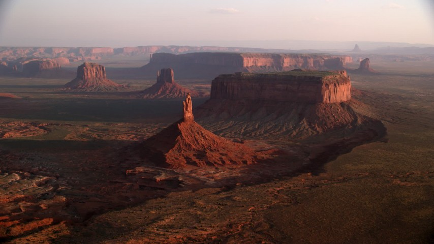 Flying by Big Indian Butte, other buttes, Monument Valley, Utah, Arizona, twilight Aerial Stock Footage AX133_132