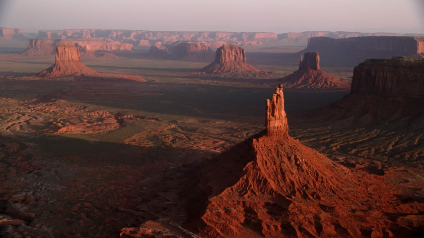 Approach Big Indian Butte, other buttes, Monument Valley, Utah, Arizona, twilight Aerial Stock Footage | AX133_134