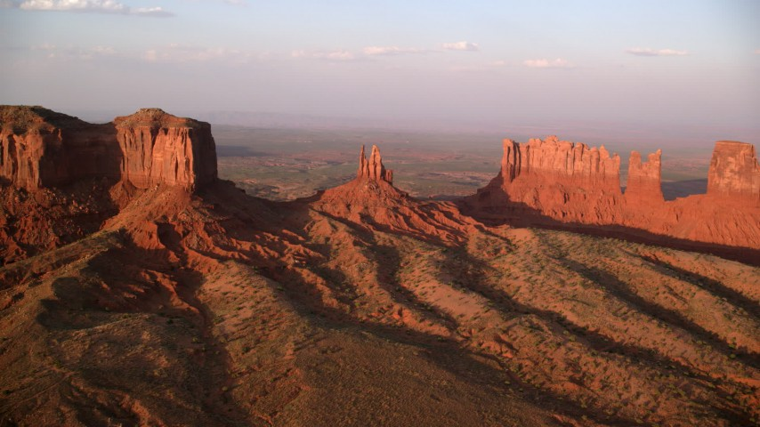 Approaching buttes, valley in background, Monument Valley, Utah, Arizona, twilight Aerial Stock Footage | AX133_140