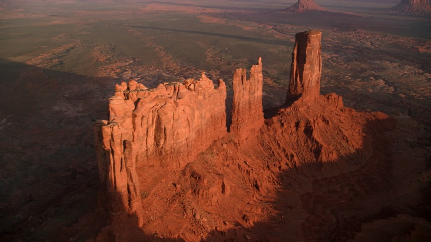 Flying away from buttes, Monument Valley, Utah, Arizona, sunset Aerial Stock Footage | AX133_143