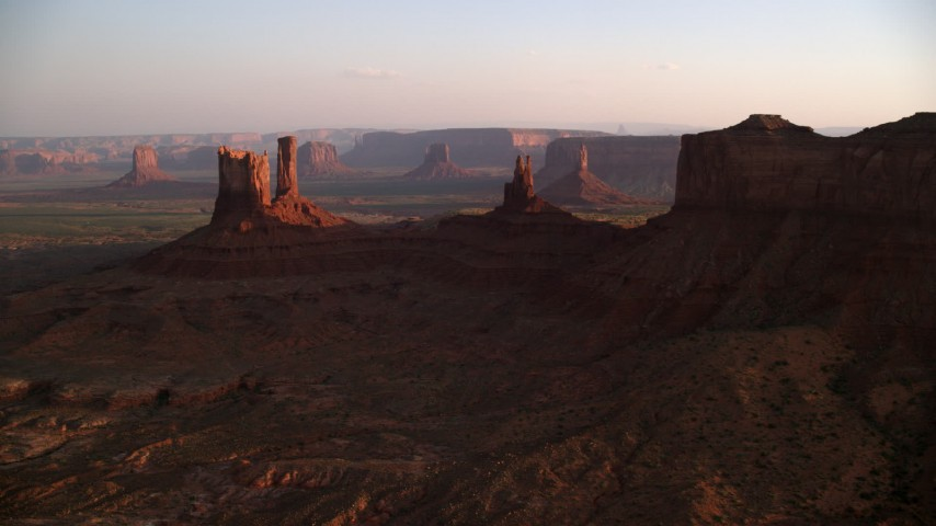 6K stock footage aerial video of flying by several buttes in Monument Valley, Utah, Arizona, twilight Aerial Stock Footage | AX133_144