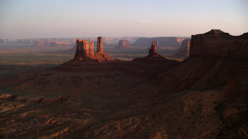 Flying by buttes, Monument Valley, Utah, Arizona, sunset Aerial Stock Footage | AX133_145