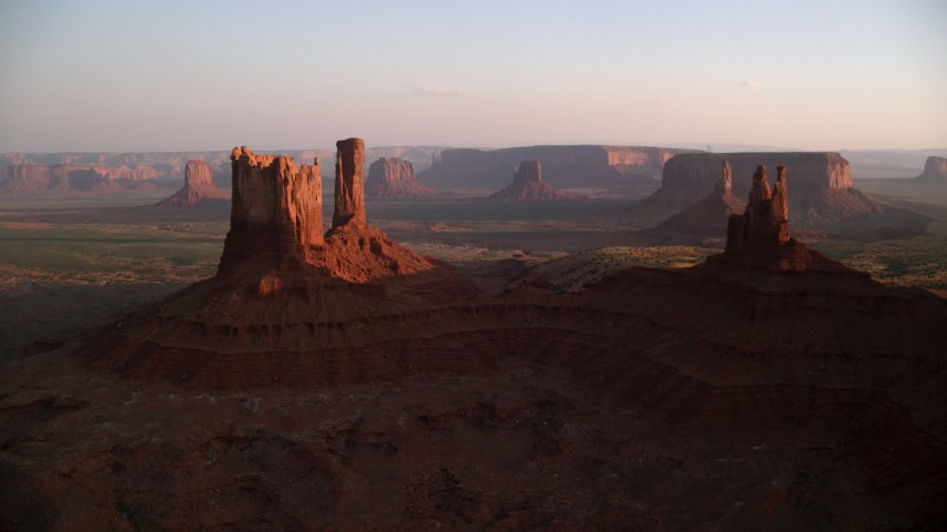 Flying by buttes, Monument Valley, Utah, Arizona, sunset Aerial Stock Footage | AX133_147