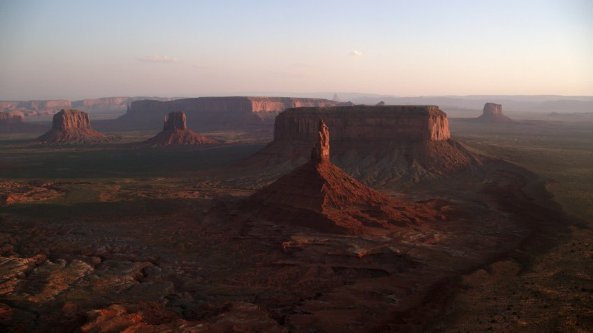Flying by buttes and mesas, Monument Valley, Utah, Arizona, sunset Aerial Stock Footage | AX133_152