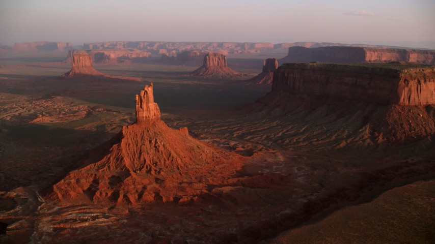 Flying by buttes and mesas, Monument Valley, Utah, Arizona, sunset Aerial Stock Footage | AX133_155