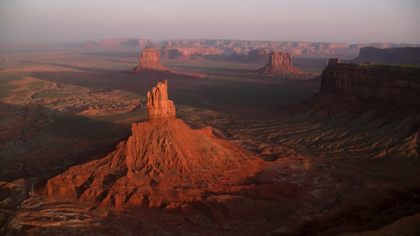 Flying by buttes, desert valley, Monument Valley, Utah, Arizona, sunset Aerial Stock Footage | AX133_156