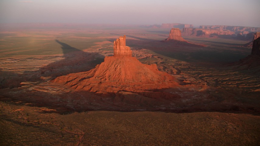 Flying away from buttes in desert valley, Monument Valley, Utah, Arizona, sunset Aerial Stock Footage | AX133_157