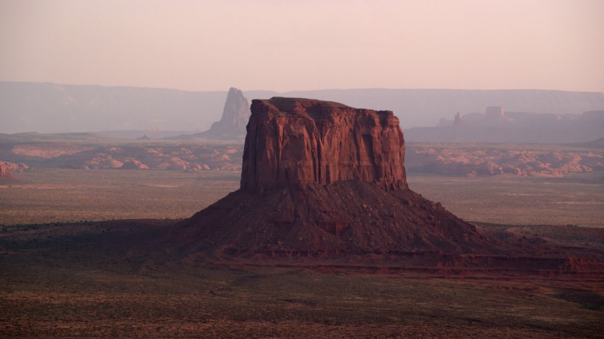 Flying by Mitchell Butte, Monument Valley, Utah, Arizona, sunset Aerial Stock Footage | AX133_158