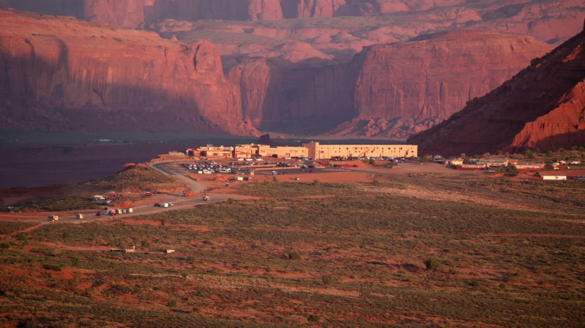 Flying by The View Hotel, Monument Valley, Utah, Arizona, sunset Aerial Stock Footage | AX133_160
