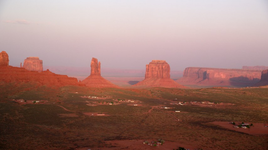 Flying by buttes, desert valley, Monument Valley, Utah, Arizona, sunset Aerial Stock Footage | AX133_163