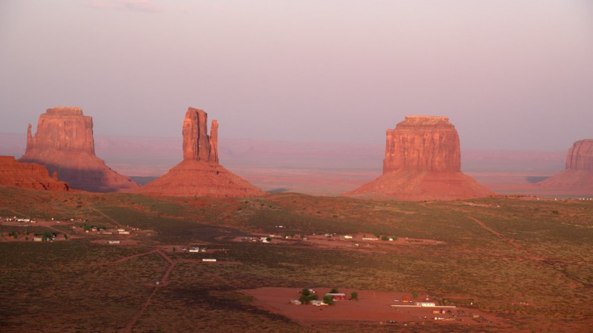 Flying by buttes, desert valley, Monument Valley, Utah, Arizona, sunset Aerial Stock Footage | AX133_164