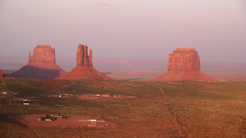 Flying by buttes, desert valley, Monument Valley, Utah, Arizona, sunset Aerial Stock Footage | AX133_165