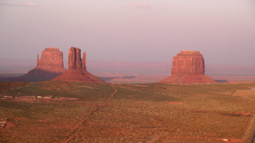 Flying by buttes, revealing a road, Monument Valley, Utah, Arizona, sunset Aerial Stock Footage | AX133_166