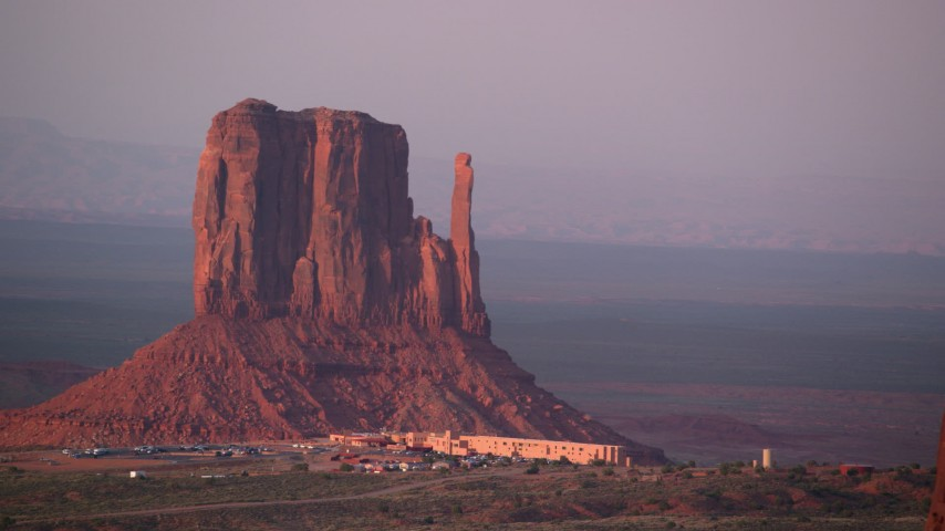 Fly by West Mitten Butte, The View Hotel, Monument Valley, Utah, Arizona, sunset Aerial Stock Footage | AX133_173