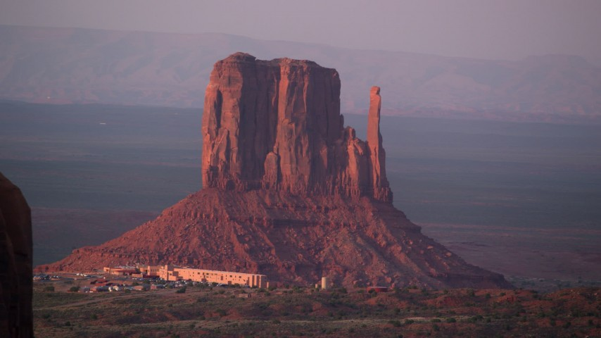 Fly by buttes, mesa, The View Hotel, Monument Valley, Utah, Arizona, sunset Aerial Stock Footage | AX133_174