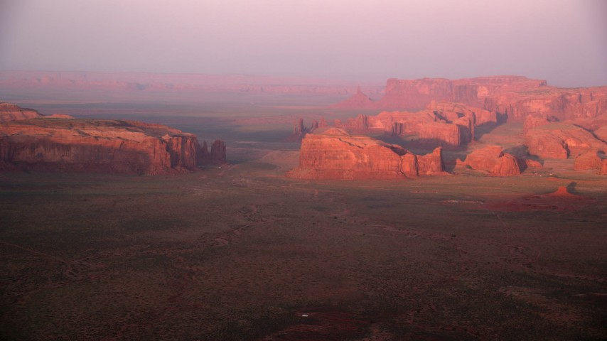 Flying by buttes and mesas, Monument Valley, Utah, Arizona, sunset Aerial Stock Footage | AX133_176