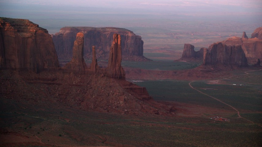 Flying by Three Sisters, Rain God Mesa, Monument Valley, Utah, Arizona, sunset Aerial Stock Footage | AX133_177