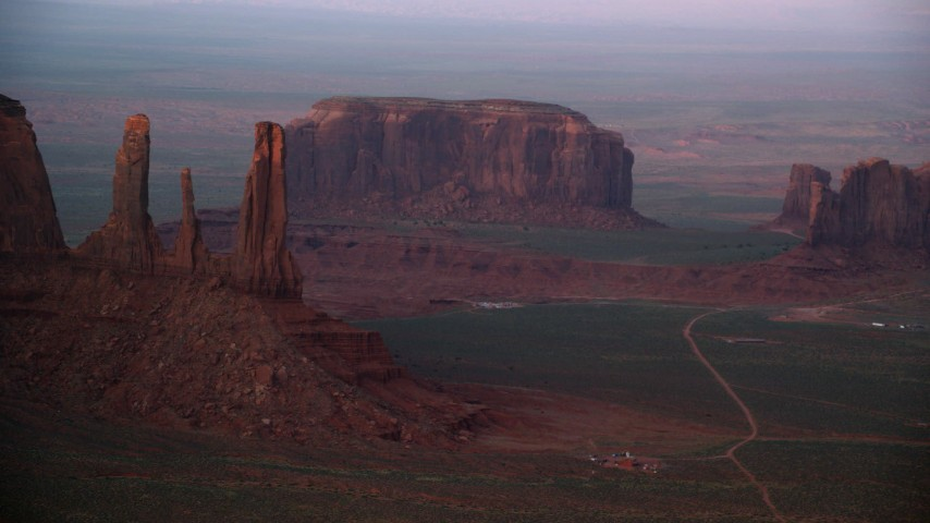 Flying by Three Sisters, Rain Got Mesa, Monument Valley, Utah, Arizona, sunset Aerial Stock Footage | AX133_178
