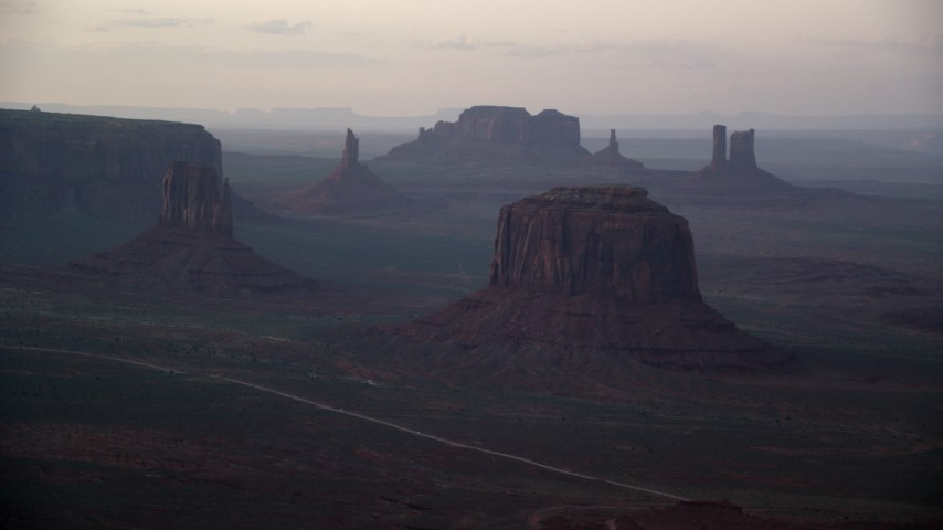 Flying by West Mitten Butte, Merrick Butte, Monument Valley, Utah, Arizona, sunset Aerial Stock Footage | AX133_183