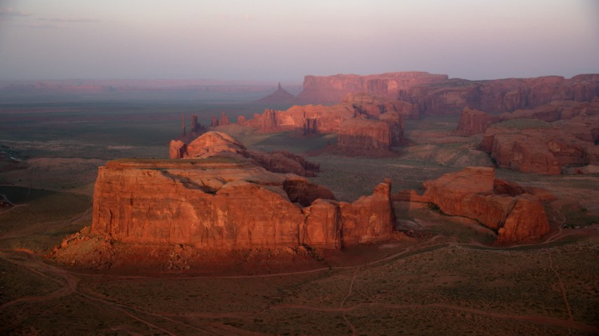 Flying by Thunderbird Mesa, Monument Valley, Utah, Arizona, sunset Aerial Stock Footage | AX133_184