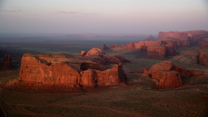 Flying by Thunderbird Mesa, Monument Valley, Utah, Arizona, sunset Aerial Stock Footage | AX133_185