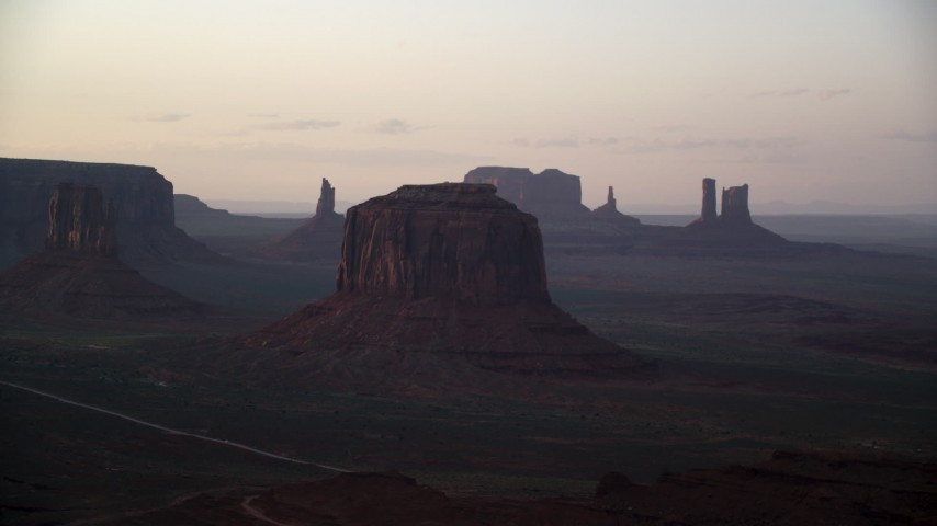 Flying by Merrick Butte, Monument Valley, Utah, Arizona, sunset Aerial Stock Footage | AX133_192