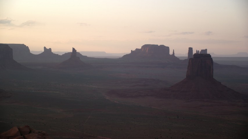 Flying by buttes, mesas, desert valley, Monument Valley, Utah, Arizona, sunset Aerial Stock Footage | AX133_195