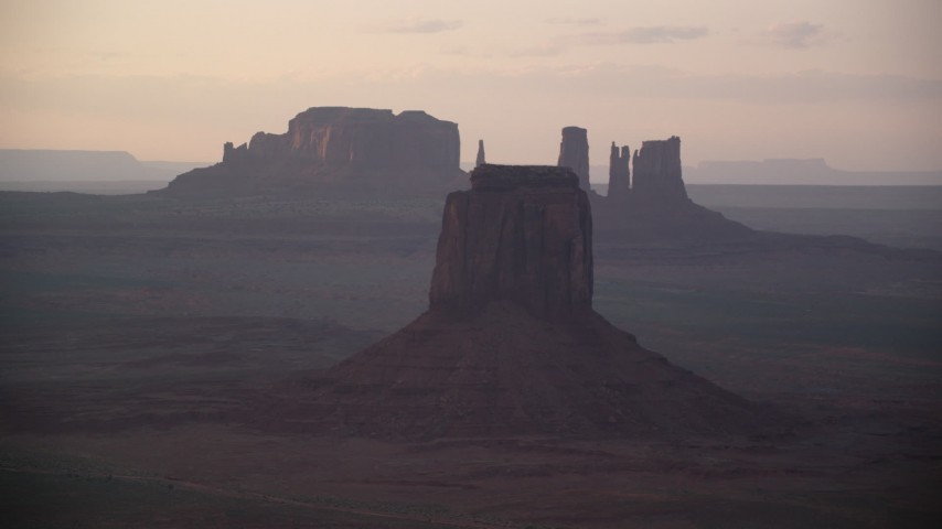 6K stock footage aerial video of East Mitten Butte in a hazy valley, Monument Valley, Utah, Arizona, sunset Aerial Stock Footage | AX133_196