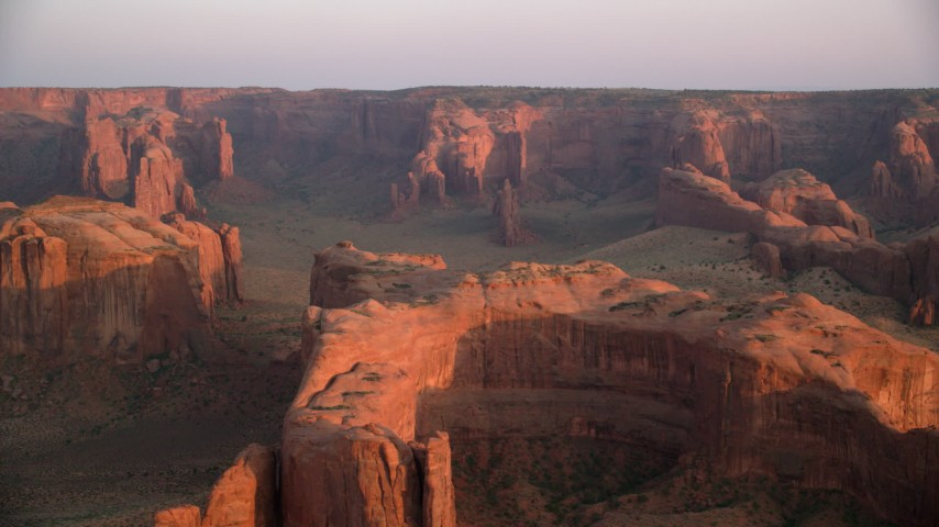 6K stock footage aerial video pan across mesa, buttes and rock formations, Monument Valley, Utah, Arizona, sunset Aerial Stock Footage | AX133_199