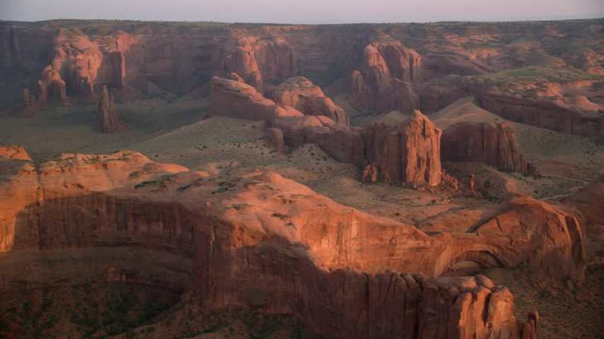 6K stock footage aerial video of flying by rock formations and Hunt's Mesa, Monument Valley, Utah, Arizona, sunset Aerial Stock Footage | AX133_200