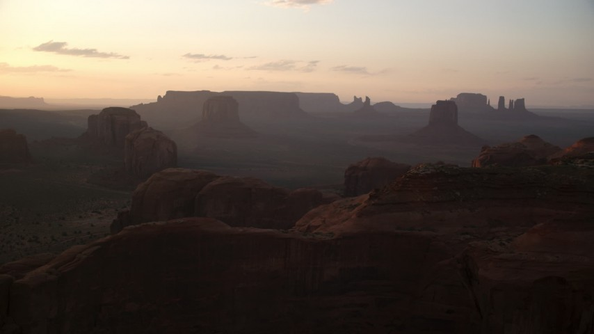 Approaching Spearhead Mesa, hazy valley, Monument Valley, Utah, Arizona, twilight Aerial Stock Footage | AX133_202