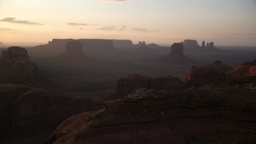 Flying by mesas and buttes, Monument Valley, Utah, Arizona, twilight Aerial Stock Footage | AX133_203
