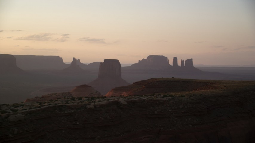 Flying by East Mitten Butte, Monument Valley, Utah, Arizona, twilight Aerial Stock Footage | AX133_204
