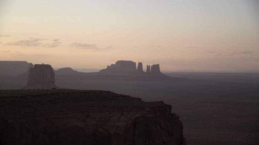 Flying by distant buttes through thick haze, Monument Valley, Utah, Arizona, twilight Aerial Stock Footage | AX133_205