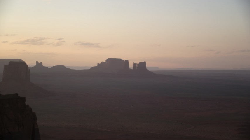 Flying by buttes, hazy desert valley, Monument Valley, Utah, Arizona, twilight Aerial Stock Footage | AX133_206