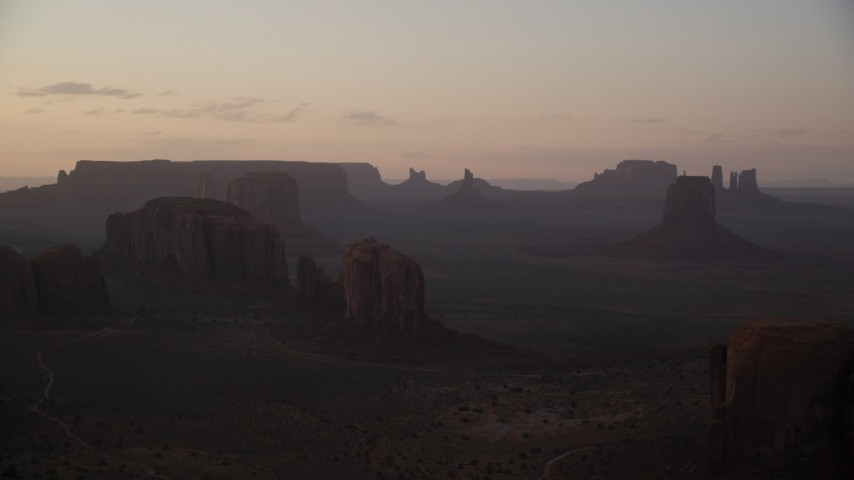 Flying by buttes and mesas, Monument Valley, Utah, Arizona, sunset Aerial Stock Footage | AX133_212
