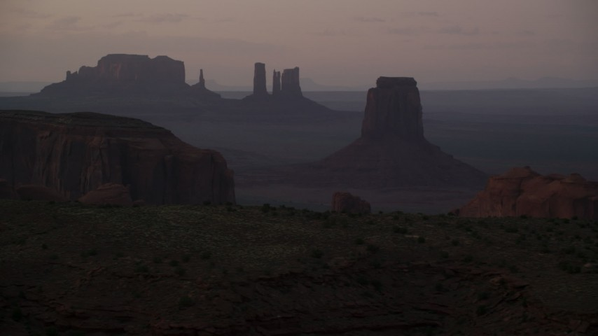 Flying by East Mitten Butte, Elephant Butte, Monument Valley, Utah, Arizona, sunset Aerial Stock Footage | AX133_214