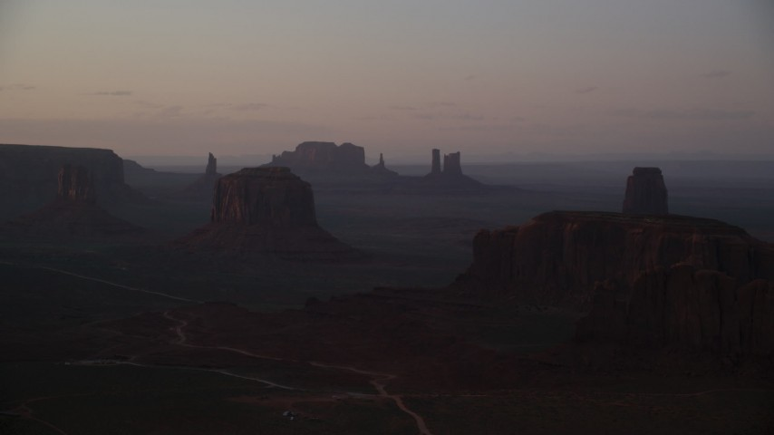 Flying by buttes in a hazy desert valley, Monument Valley, Utah, Arizona, sunset Aerial Stock Footage | AX133_216