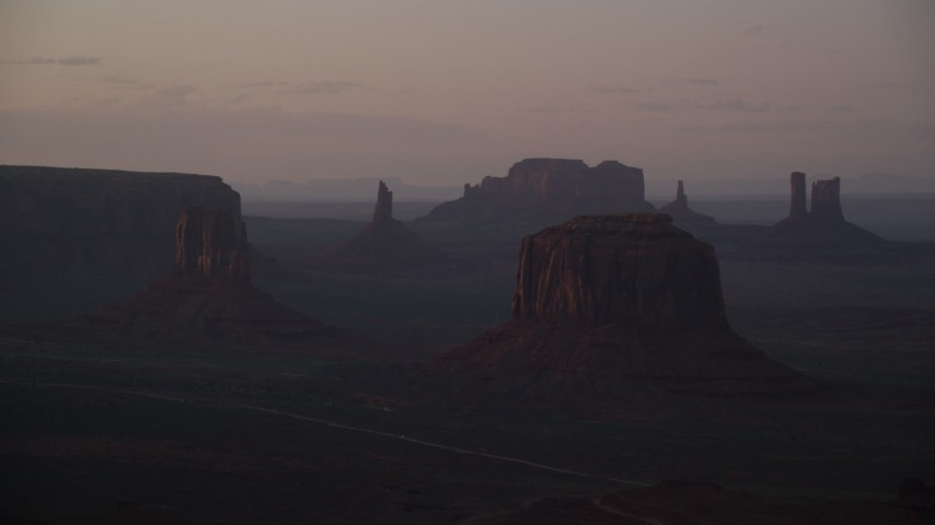 Flying by West Mitten Butte, Merrick Butte, Monument Valley, Utah, Arizona, sunset Aerial Stock Footage | AX133_217