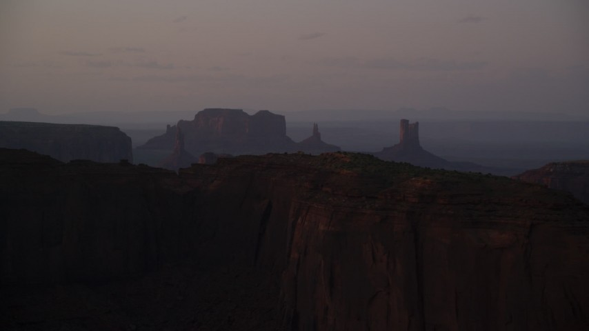 6K stock footage aerial video of top of Mitchell Mesa, distant buttes, Monument Valley, Utah, Arizona, twilight Aerial Stock Footage | AX133_220