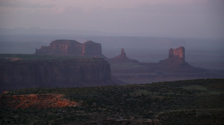 Flying by mesas and buttes, Monument Valley, Utah, Arizona, twilight Aerial Stock Footage | AX133_223