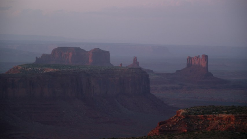 6K stock footage aerial video of mesas and buttes in the hazy valley, Monument Valley, Utah, Arizona, twilight Aerial Stock Footage | AX133_224