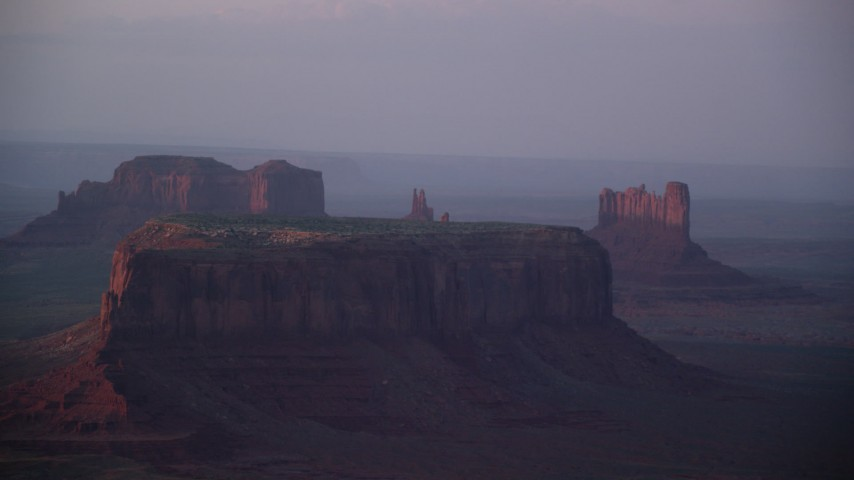 Flying by mesas and buttes, Monument Valley, Utah, Arizona, twilight Aerial Stock Footage | AX133_225